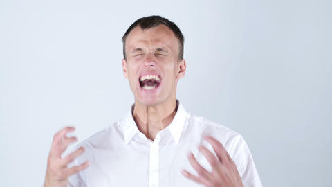 Close-up of angry businessman screaming against blue background Footage