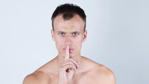 Portrait of handsome shirtless man showing silent gesture, white background Footage