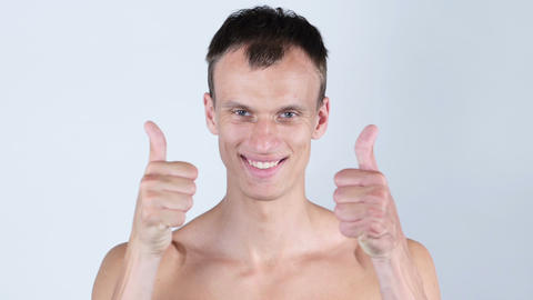 Portrait of young shirtless man shows thumbs up with both hands Footage