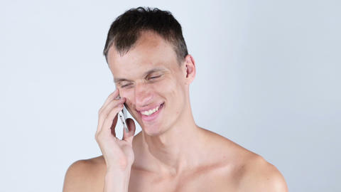 Portrait of cheerful handsome shirtless man talking on the phone Footage