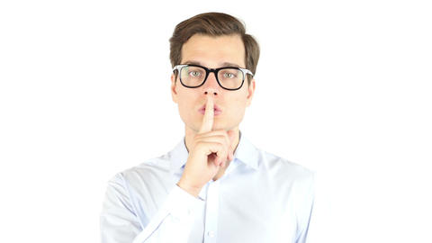 Portrait of businessman making silence gesture , isolated white background Footage