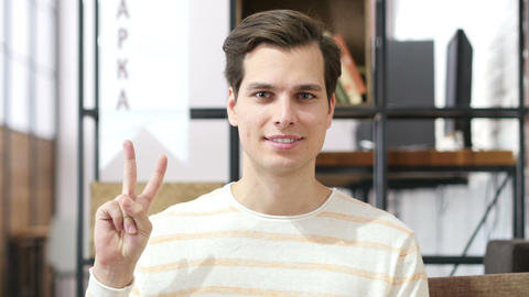 Young man showing victory sign , success in investment Footage