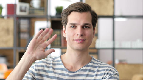 Portrait of young relaxed business man waving hand to camera, designer Footage