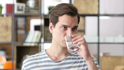 Handsome businessman in casual cloth drinking water in office Footage