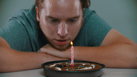 A man is blowing out a candle on a birthday cake Live Action
