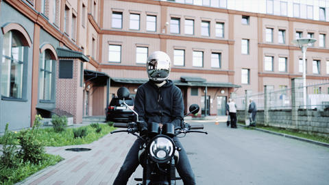 Young man and biker in helmets on motorcycle in city with urban background Live Action