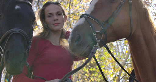 Caucasian girl with problem skin and long brown hair holding bridles of two Footage