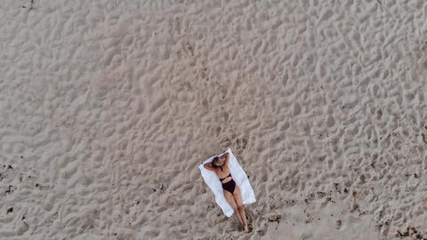 Beautiful girl alone on a sandy beach at the ocean Footage