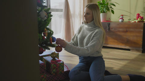 Beautiful woman decorating christmas tree with toys by the window GIF