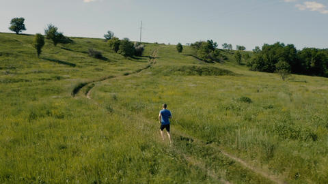 Man runner run outdoor in the field. Airial video from drone Footage