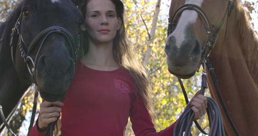 Sad Caucasian woman with problem skin holding bridles of two horses outdoors Footage