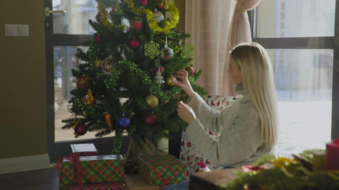 Pretty girl in sweater decorates Christmas tree by yellow balls. Beautiful Footage