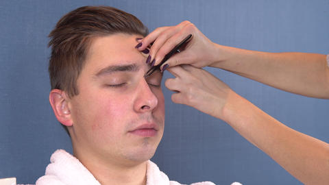 A young man plucked eyebrows in a spa salon. Woman tweezers pulls out eyebrows Live Action