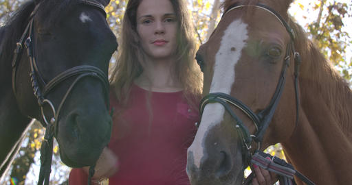 Caucasian girl with problem skin and long brown hair standing with two horses Footage