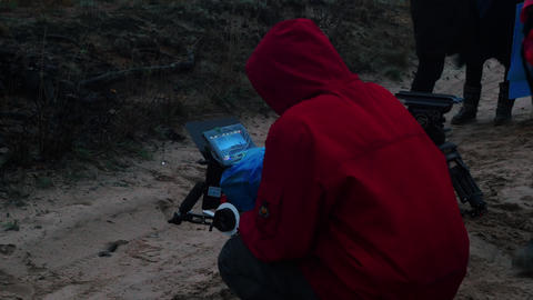 A man in red jacket holding a camera and filming cinema scene in the forest Footage