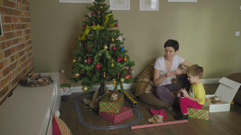 Child and woman decorating christmas tree GIF