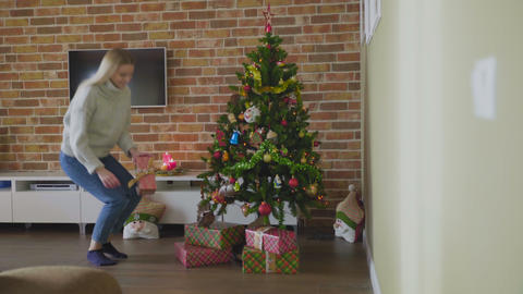 Pretty woman putting gift under christmas tree in luxury house GIF