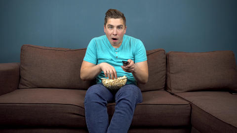A young man is watching TV and eating popcorn. The guy is watching TV carefully Live Action