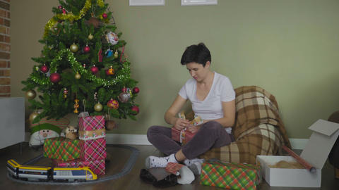 Young Woman Wrapping Christmas Gifts With Paper At Home GIF