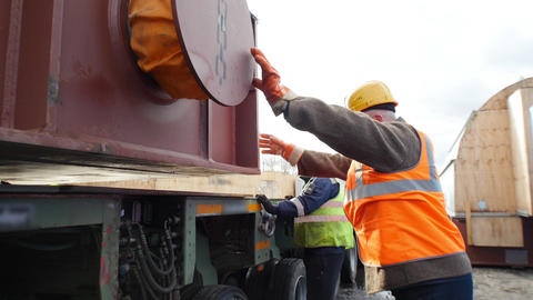 Cargo shipping - men working on the construction site - helping to set cargo on Live Action