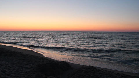 Baltic Sea coast during scarlet sunset. Waves on seashore in evening Live Action