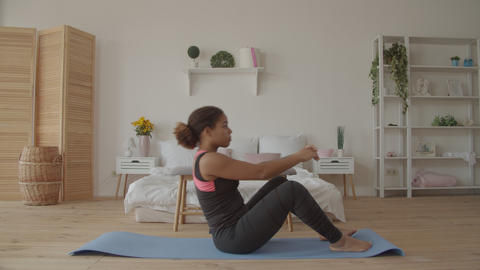 Determined fitness woman doing sit-ups at home Live Action