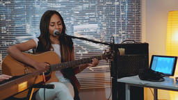 Mixed-race young lady playing guitar and singing into microphone during band Footage
