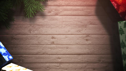 Animated closeup gift boxes and green tree branches on wood background Animation