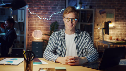 Office worker in casual clothing smiling looking at camera in office at night Footage