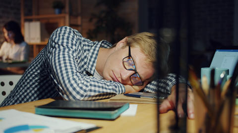 Slow motion of handsome guy sleeping on table in dark office relaxing at work Footage