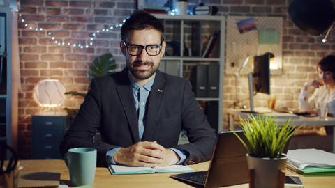 Joyful businessman in glasses smiling in office in the evening sitting at desk Footage