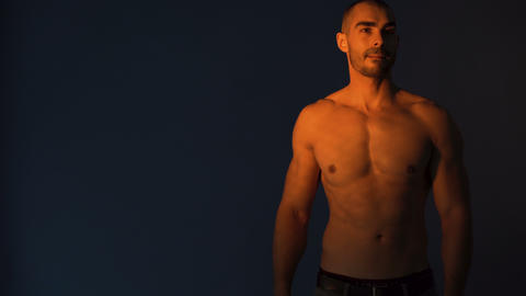 Attractive fitness model showing great body against black background Footage