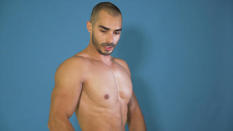 Male Fitness model posing and showing triceps muscles, isolated on blue Footage