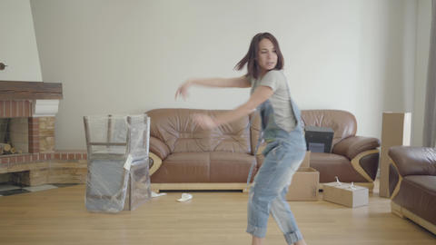 Young cheerful Caucasian woman dancing in the living room with unpacked Footage