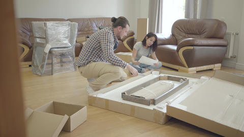 Young positive Caucasian family unpacking parcel in the living room. Happy Footage
