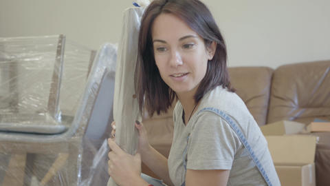 Young smiling Caucasian woman unpacking parcel in the living room. Pretty girl Footage
