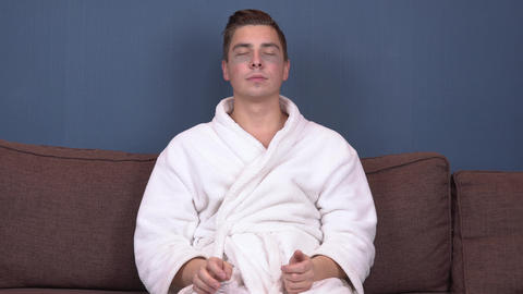 A young man with patches on his face relaxes. Spa treatments. Blue hydrogel Footage