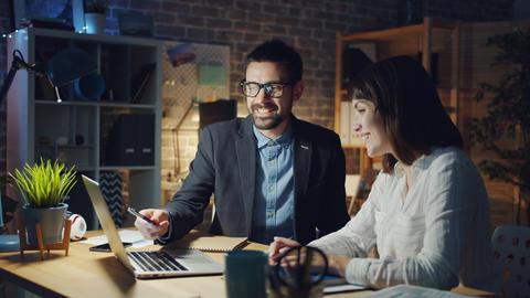 Joyful business people speaking laughing using laptop at work in office at night Footage
