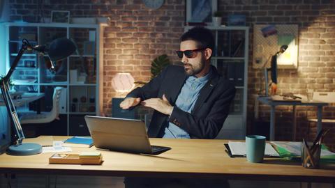 Joyful man in glasses enjoying music working with laptop dancing in dark office Footage