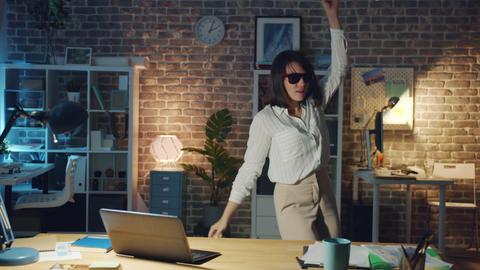 Joyful girl in stylish glasses dancing in workplace having fun alone at night Footage
