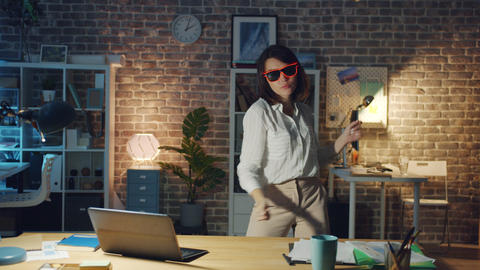Beautiful woman in funny glasses relaxing in office at night dancing having fun Footage