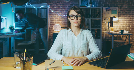 Time lapse of beautiful lady in glasses looking at camera at desk in office Footage
