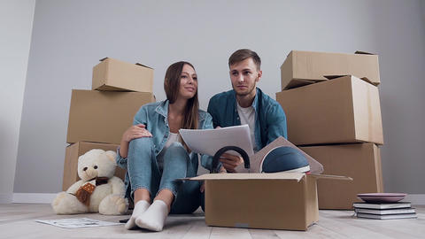 Attractive happy smiling couple sitting on the floor and planning interier for Footage