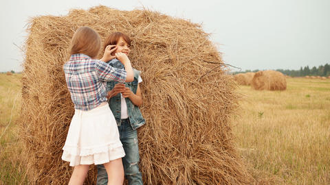 Happy boy and girl playing on haystack in field Live Action
