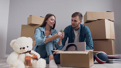 Agreeable happy young couple in love having fun together while unpacking Footage