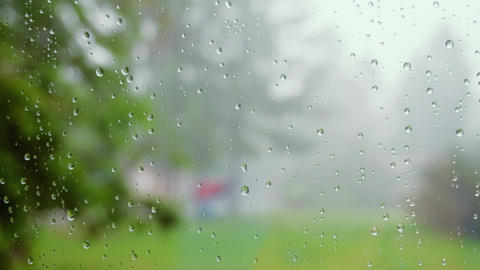 Close up of water drops on glass. Rain drops flow down the surface of the glass Live Action