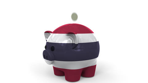 Coins fall into piggy bank painted with flag of Thailand. National banking Live Action