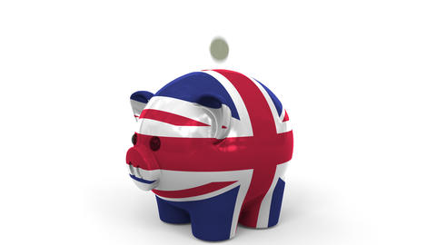 Coins fall into piggy bank painted with flag of Great Britain. National banking Live Action