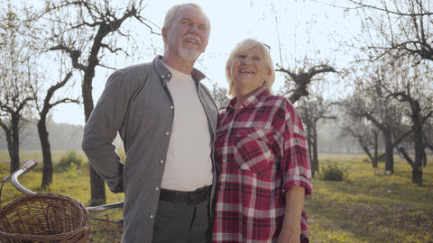 Portrait of a happy senior Caucasian couple standing in sunlight in the foggy Footage