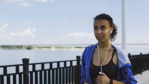 Young beautiful African American girl with headphones running along the GIF